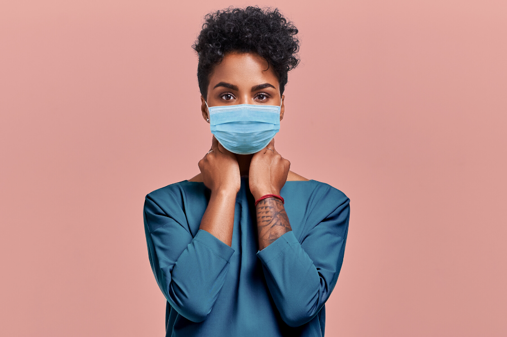 Black woman entrepreneur with Afro hairstyle wearing protective mask against COVID virus